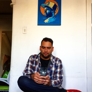 Oslec sits in his home in Santiago beneath a painting of J. Dilla.